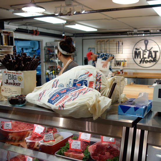 The meat counter at The Meat Hook, where you can see butchers dressing the meat.