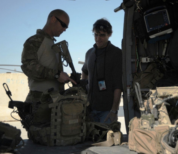 A pararescue soldier holding an M4 discusses gear with Phil Scott as the helicopter is loaded.