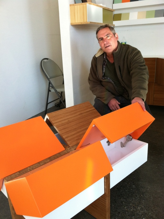 David Gotl lifts the four cubby covers of the streamlined coffee table,